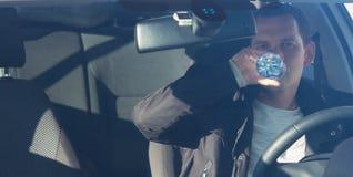 司机人饮用水,当驾驶汽车,看法通过有过滤器的时挡风玻璃 免版税库存图片