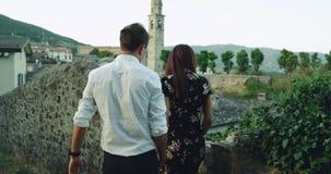 变冷在老街道下的浪漫美好的年轻夫妇在意大利,他们停止了此外老石篱芭和 影视素材