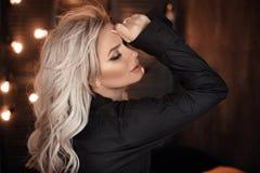发型 摆在黑衬衣的美丽的白肤金发的妇女画象 在bokeh光黑暗的背景的时兴的白肤金发的女孩模型 库存照片