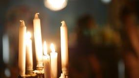 发火焰一些个的蜡烛,移动在黑背景的某人在蜡烛后 股票录像