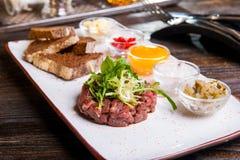 发牢骚鞑靼用芝麻菜沙拉、酥脆面包芯片、调味汁和快餐在白色板材在服务的餐馆桌上 库存图片