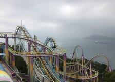 吸引力紫色和黄色高过山车好久在海洋公园游乐场在阴暗天空和海湾中的香港 图库摄影