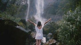 后面有自由的胳膊大开享用的片刻的看法愉快的年轻旅游妇女在史诗斯里兰卡密林瀑布的 影视素材