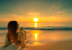 后面看法性感,享用并且放松说谎在与草帽的沙滩的女服比基尼泳装在热带海放松和享受假日 免版税图库摄影