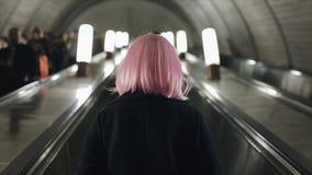 后面观点的有桃红色头发的妇女使用在地铁的自动扶梯 影视素材