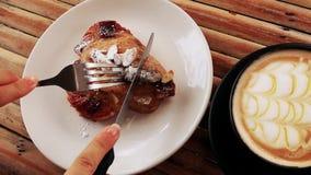 吃与叉子的新近地被烘烤的杏仁新月形面包和刀子用在咖啡馆的咖啡 顶视图 股票录像
