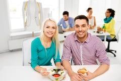 吃午餐和吃在办公室的愉快的同事 库存图片