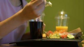 吃在咖啡馆、汽水和汁液的女性顾客新鲜的沙拉在塑料盘子 股票视频