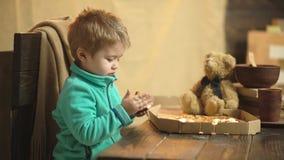 吃在木背景的逗人喜爱的男孩比萨 在木背景的可口比萨 有吃比萨的一头软的熊的男孩 影视素材