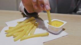 吃薯条用在咖啡馆的乳酪调味料的妇女 特写镜头手 股票录像
