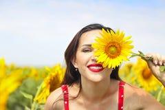 向日葵领域的俏丽的深色的妇女 免版税库存图片
