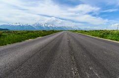 向盛大Tetons的柏油碎石地面路 库存照片
