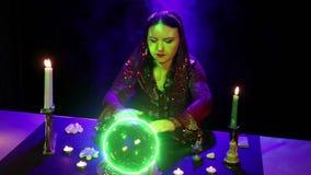 吉普赛算命先生一定在桌上参与与发光绿色的一个水晶球的魔术 影视素材