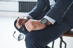坐与被烙记的手表的椅子在他的手上并且拿着玻璃一个时髦的商人的特写镜头图象 免版税图库摄影