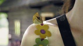 坐妇女的肩膀和挥动它的翼的蝴蝶 股票视频