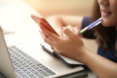 坐在书桌和工作在计算机关闭的妇女在手上 免版税库存照片