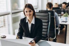 坐在她的工作场所的一名愉快的女实业家的画象在办公室 图库摄影
