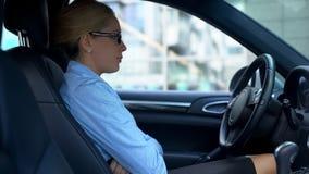 坐在她的汽车的歇斯底里的女实业家用横渡的手,问题在工作 库存图片