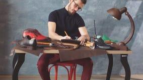 坐在桌和画的模型上的鞋类设计师 股票录像
