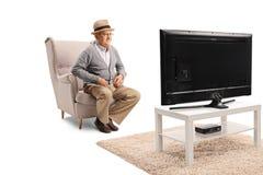 坐在扶手椅子和观看的电视的老人 免版税库存图片