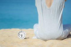 坐在白色闹钟旁边的一件灰色礼服的亚裔妇女安置在沙子 蓝色海和天空作为背景 概念为 免版税库存照片