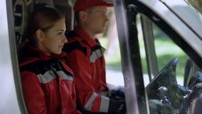 坐在运输,专业紧急医疗的救护车乘员组 免版税库存图片