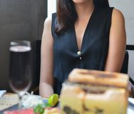 坐在餐馆的典雅的年轻女人 免版税库存照片