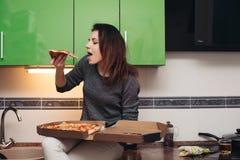 坐厨房和吃鲜美比萨的饥饿的女孩 免版税库存图片