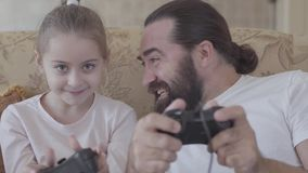 坐沙发和演奏电子游戏有他小的女儿关闭的有胡子的人藏品控制杆 概念  股票录像