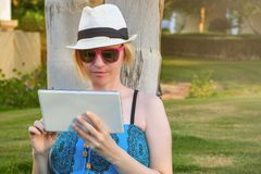 坐绿草在公园和拿着片剂计算机的年轻学生妇女 免版税库存图片
