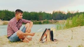 坐由单独火的年轻可爱的人 在棍子的油炸物蛋白软糖 以森林为背景和 股票录像