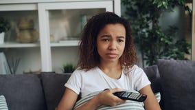 坐舒适的沙发和哭泣在哀伤的电影的情感年轻非裔美国人的女孩看着电视放大  影视素材
