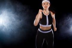 坚强的运动妇女短跑选手,跑在佩带在运动服的黑背景 健身和体育刺激 运行 图库摄影