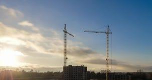 塔吊的剪影时间间隔运转在一个多层的大厦的工地工作的在落日的光芒的