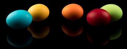 复活节彩蛋横幅 在黑背景的五颜六色的复活节彩蛋与反射 现代的设计 库存图片