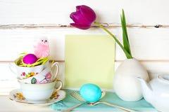 复活节快乐茶党或膳食邀请与茶杯、桃红色小鸡、花、鸡蛋和银器的卡片在现代异想天开的安排 免版税图库摄影