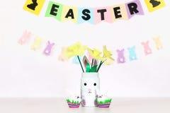 复活节的Diy装饰 纸诗歌选,花瓶兔宝宝,黄水仙,蛋兔宝宝,篮子用被绘的鸡蛋 免版税图库摄影