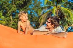 夏天父亲和儿子生活方式画象坐在海滩的橙色可膨胀的沙发热带海岛 库存照片