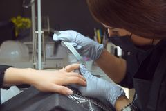 大师做修指甲 在美容院的松弛天 修指甲师大师在妇女` s手做修指甲 女孩油漆钉子 图库摄影