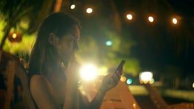大气透镜火光坐在夜休息室海滩酒吧椅子的被射击愉快的年轻女实业家使用智能手机应用程序 影视素材