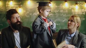 大衣服外套和毕业盖帽的孩子 教育在小学 专业家庭教师是关于他们的专家 影视素材