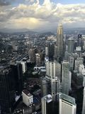 天然碱摩天大楼和塔,马来西亚,反对山和天空背景的吉隆坡的首都与云彩 免版税库存图片