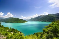 天蓝色的水在绿色山天空蔚蓝白色云彩背景中的一个蓝色盐水湖 免版税图库摄影