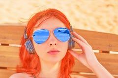 太阳镜的妇女听到在海滩的音乐的 图库摄影