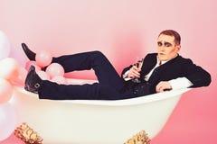 失去自己在您喜爱的饮料 笑剧人有庆祝党用香槟 模仿演员喜欢沐浴在浴 免版税图库摄影