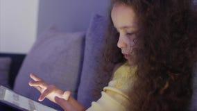 夜一个白种人逗人喜爱的孩子的射击画象,小的女婴关闭儿童的面孔观察与a的一平板电脑 影视素材