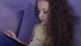 夜一个白种人逗人喜爱的孩子的射击画象,小的女婴关闭儿童的面孔观察与a的一平板电脑 股票录像