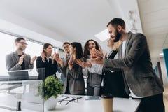多种族小组祝贺他们的上司的商人拍的手-商业公司队,在a以后的起立欢呼 免版税库存照片