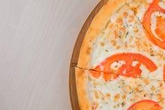处所切比萨用蕃茄和乳酪在木板 顶视图 图库摄影