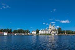 奥斯塔什科夫,SELIGER,俄罗斯:Seliger湖的尼洛夫修道院 编译的黄色 天空蔚蓝和蓝色湖在夏天 免版税库存照片